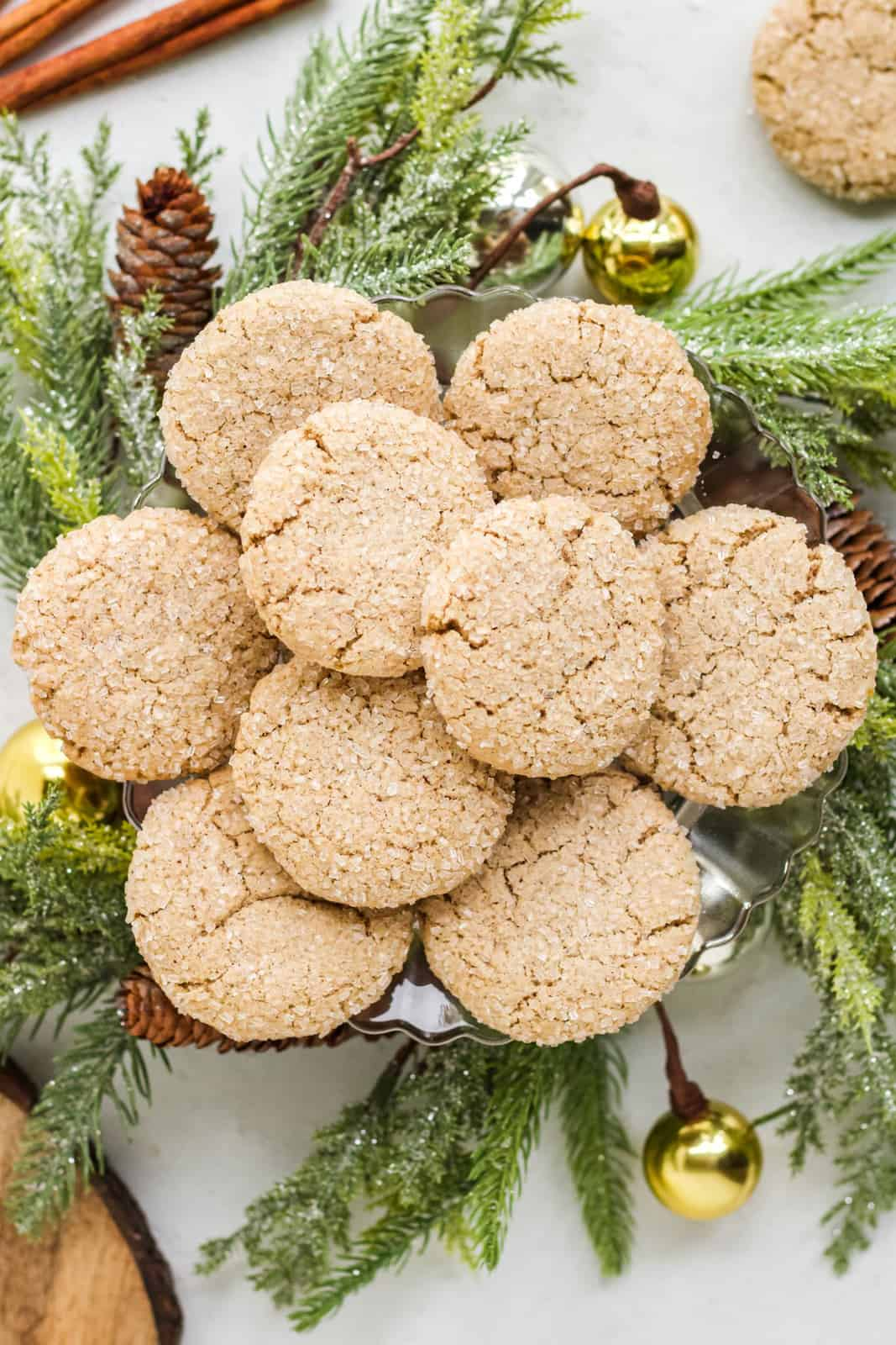 Overhead of spice cookies stacked on platter with tree sprigs