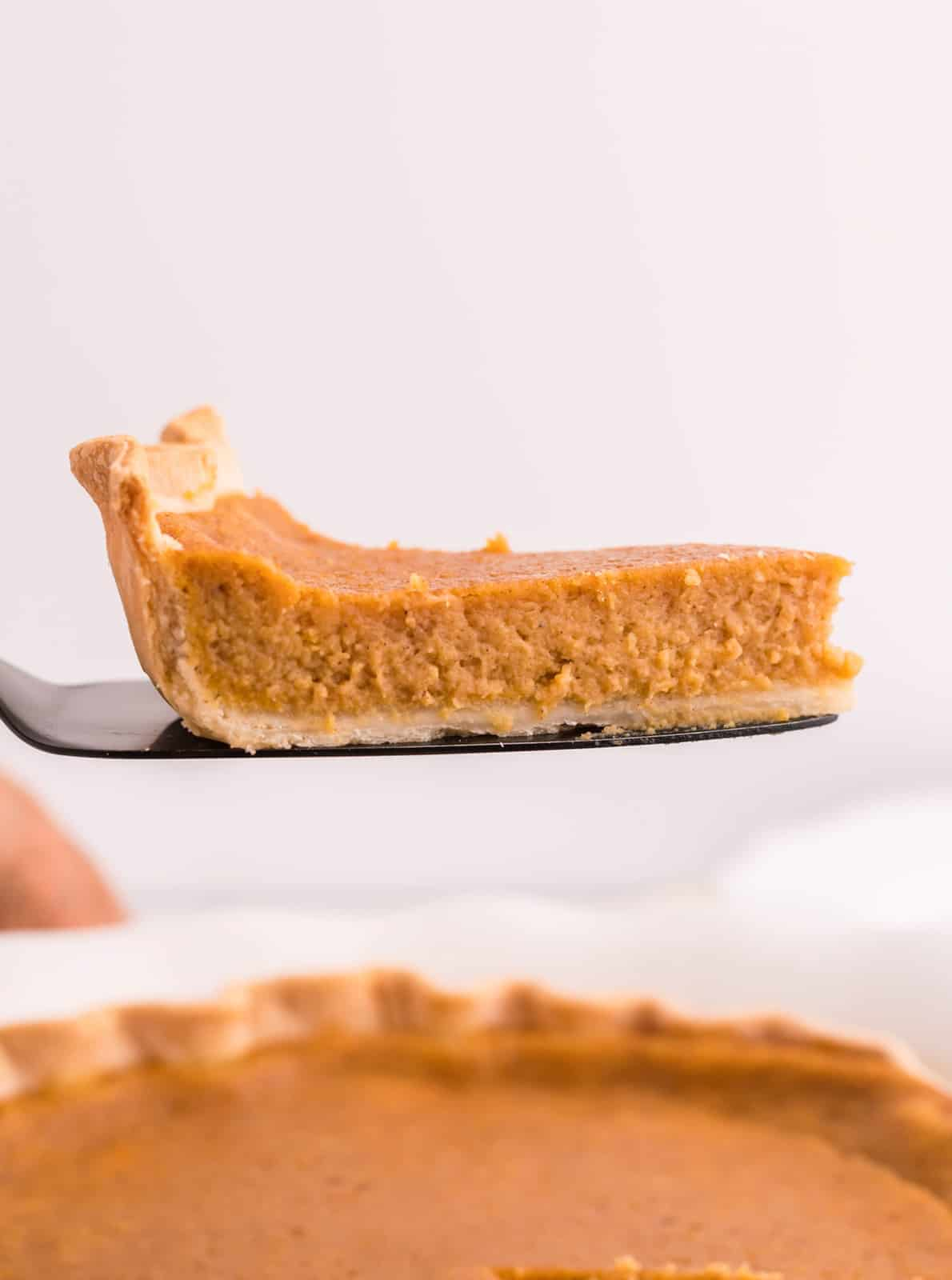 Slice of Sweet Potato Pie being lifted up on pie server