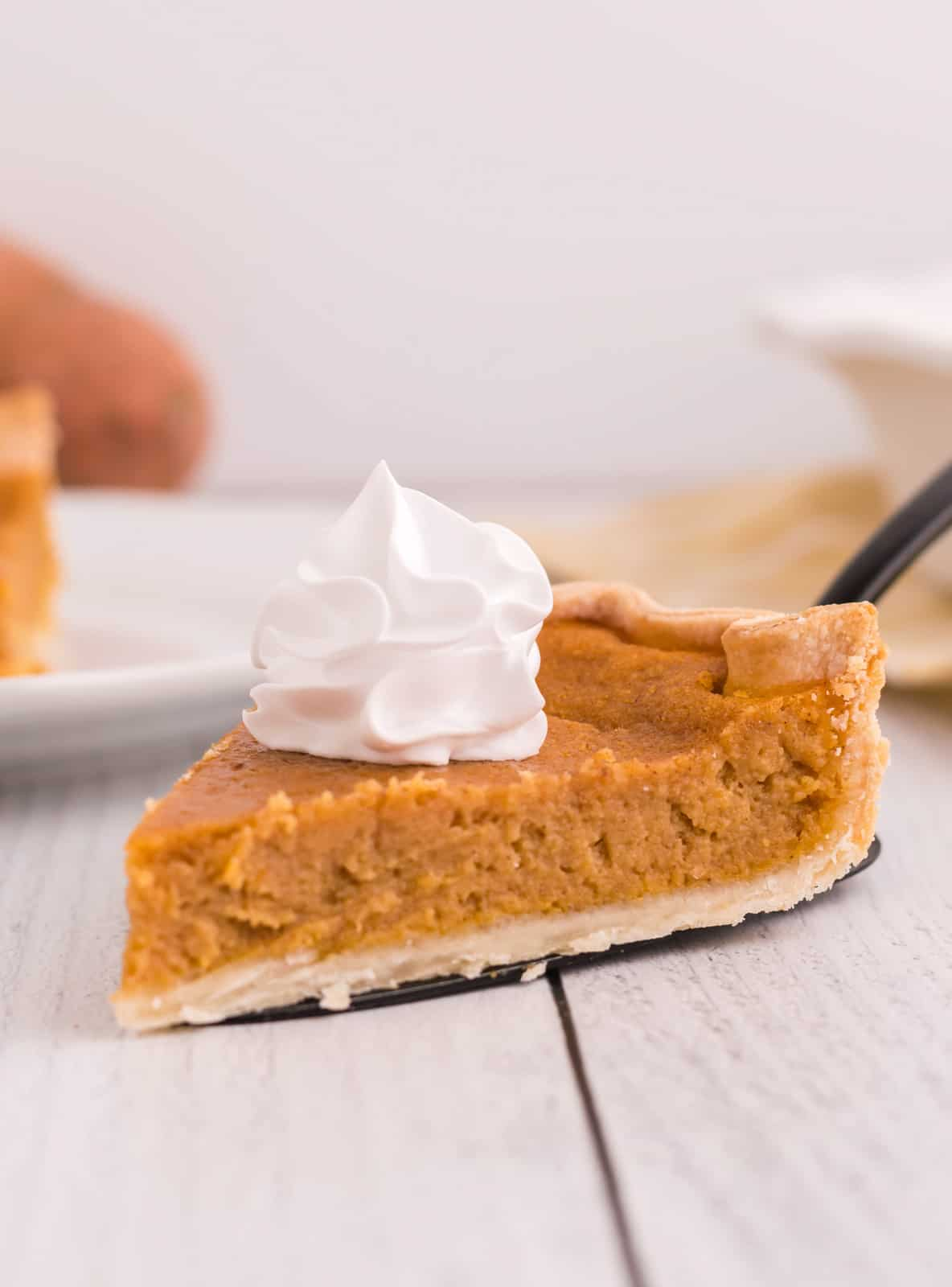 Slice of pie with dollop of whipped cream on pie server