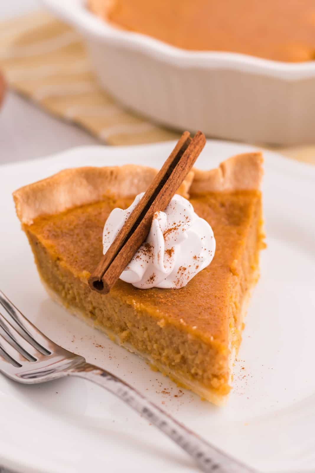 Slice of Sweet Potato Pie on white plate with whipped cream and cinnamon stick