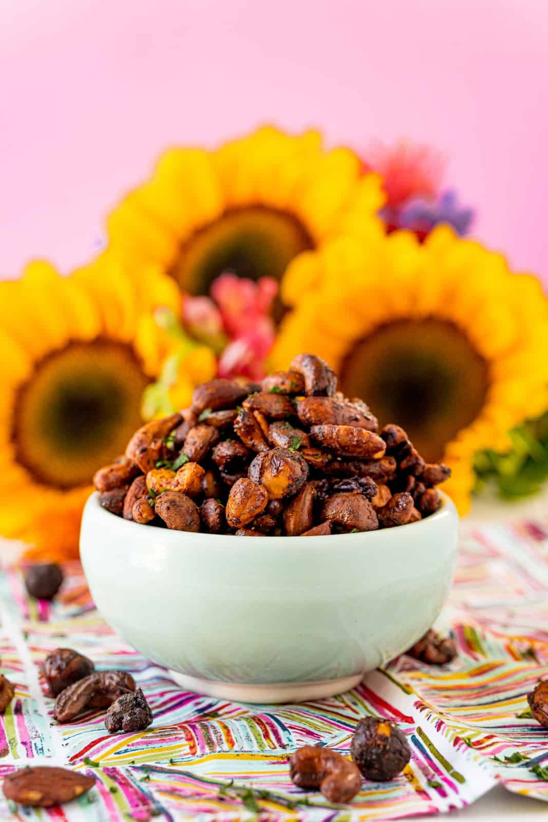 Bowl of Sweet and Spicy Roasted Nuts in front of flowers