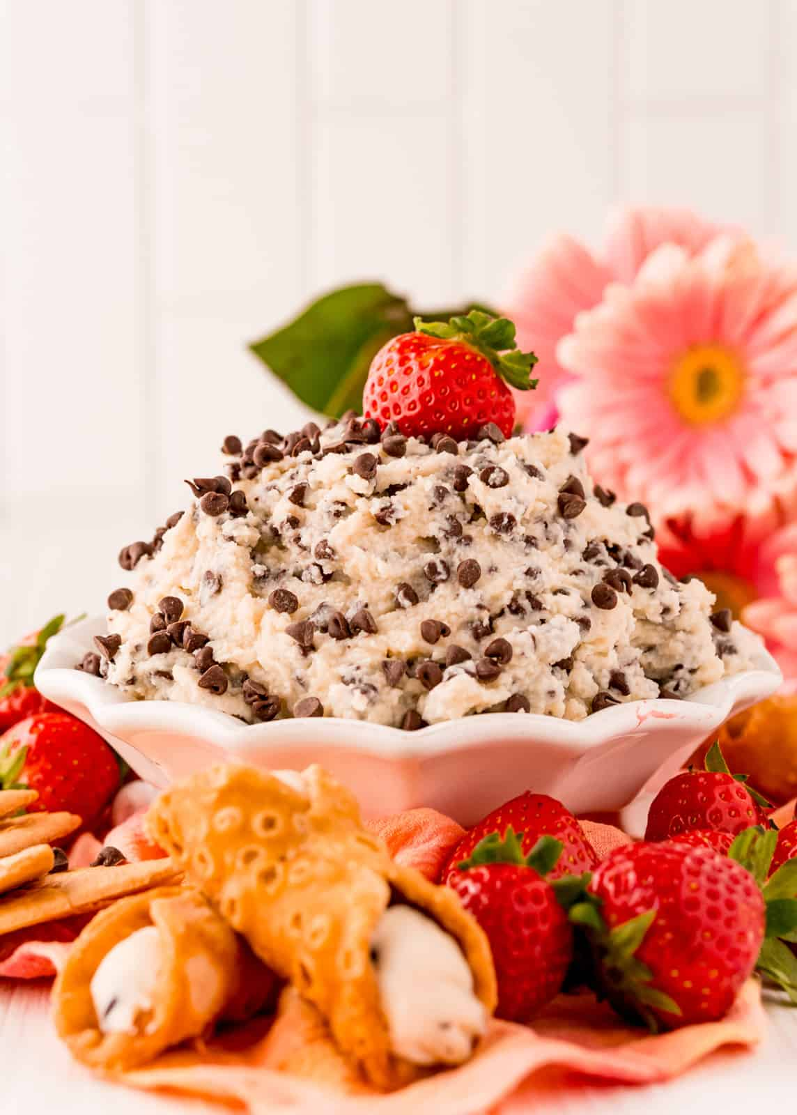 Side view of Cannoli Dip in bowl topped with strawberry