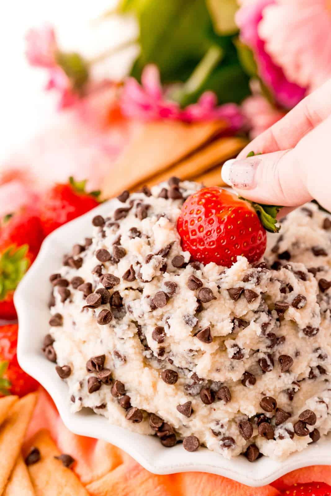 Hand dipping strawberry in Cannoli Dip