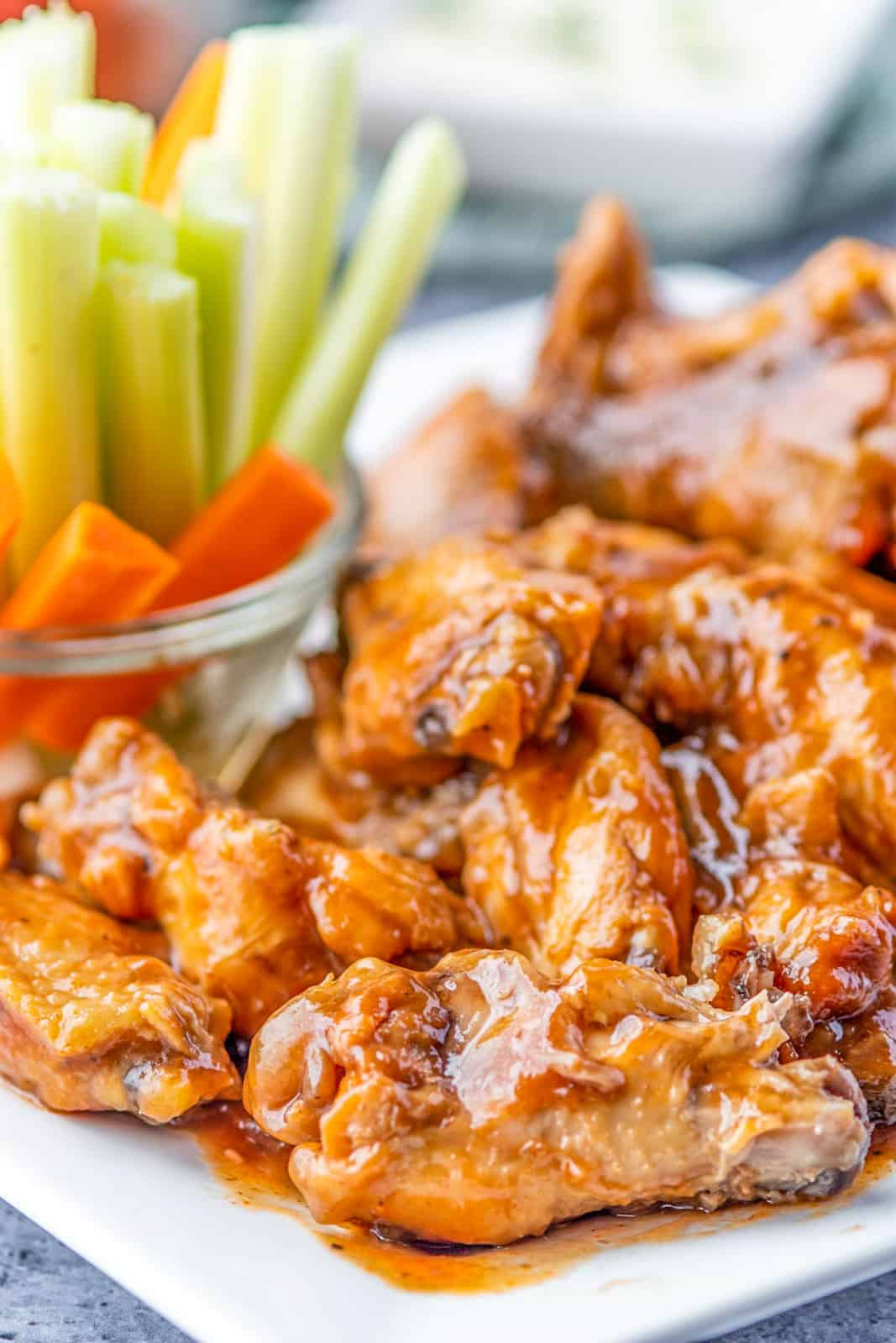 Close up of Slow Cooker Chicken wings on white plate with celery and carrots in background
