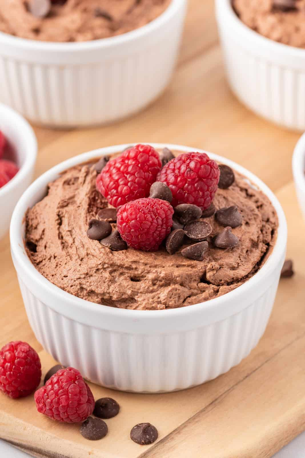 Chocolate Mousse in white ramekin topped with chocolate chips and raspberries