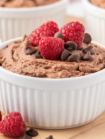 White Ramekin filled with Easy Chocolate Mousse topped with chocolate chips and raspberries square image