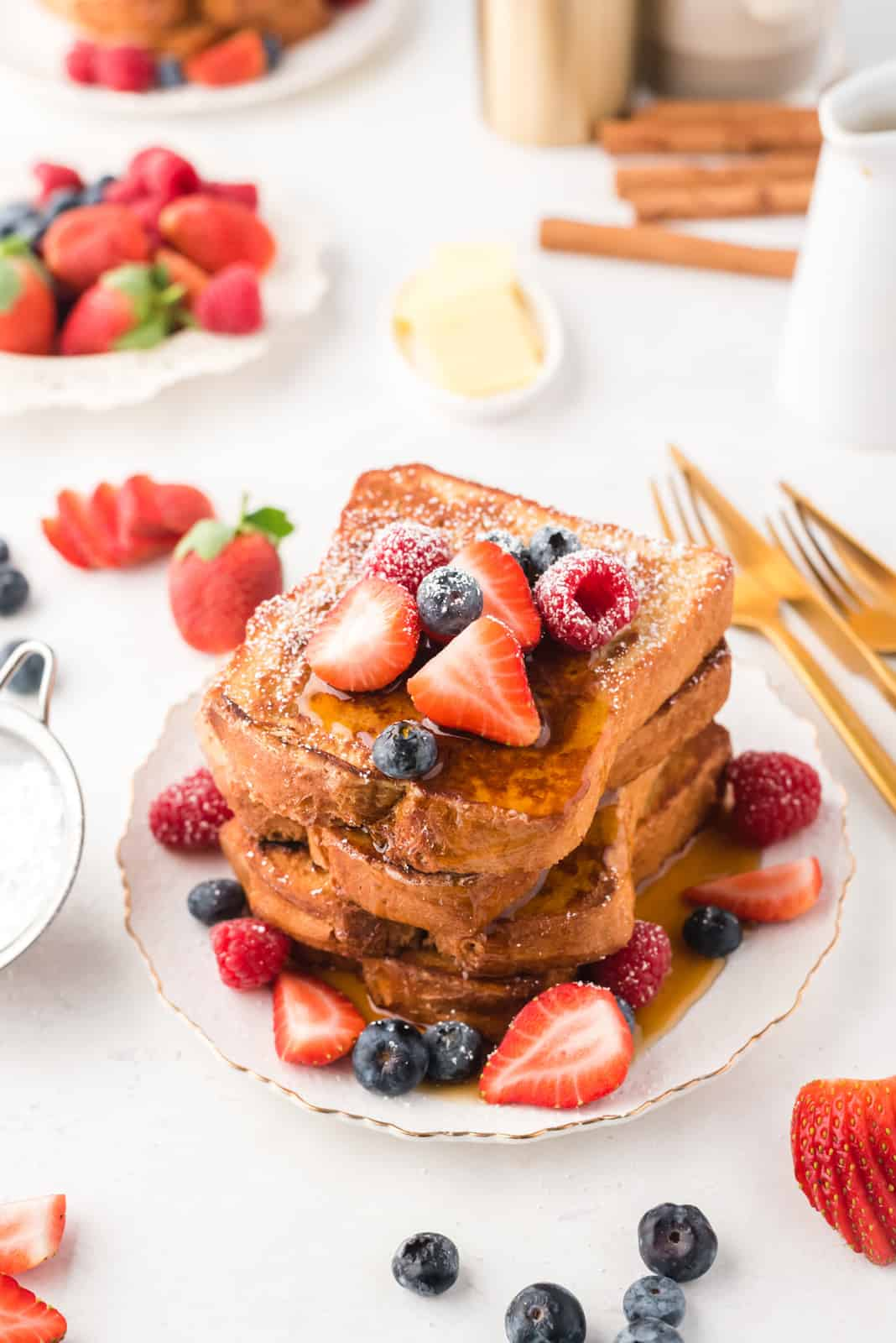 Plate of syrup covered Stacked French Toast Recipe with fruit