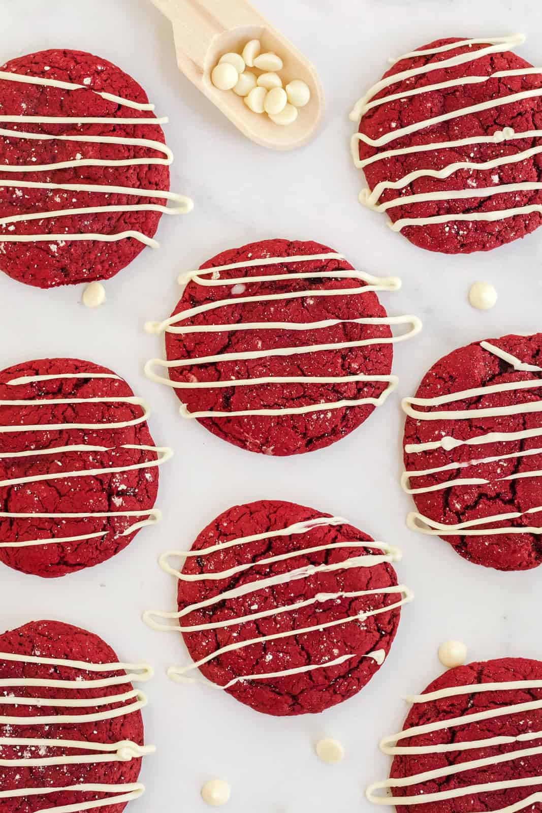 Overhead of white chocolate drizzled red velvet cheesecake cookies
