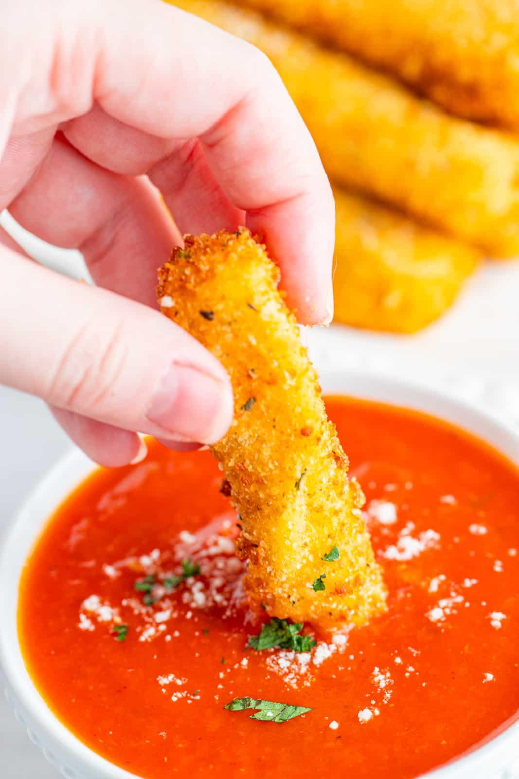 Hand dipping one Mozzarella Stick into marinara sauce