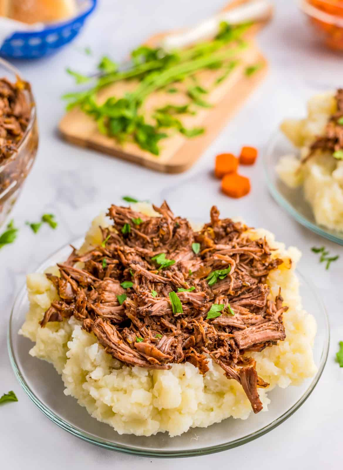 Close up of Slow Cooker Beef Short Ribs over mashed potatoes topped with parsley