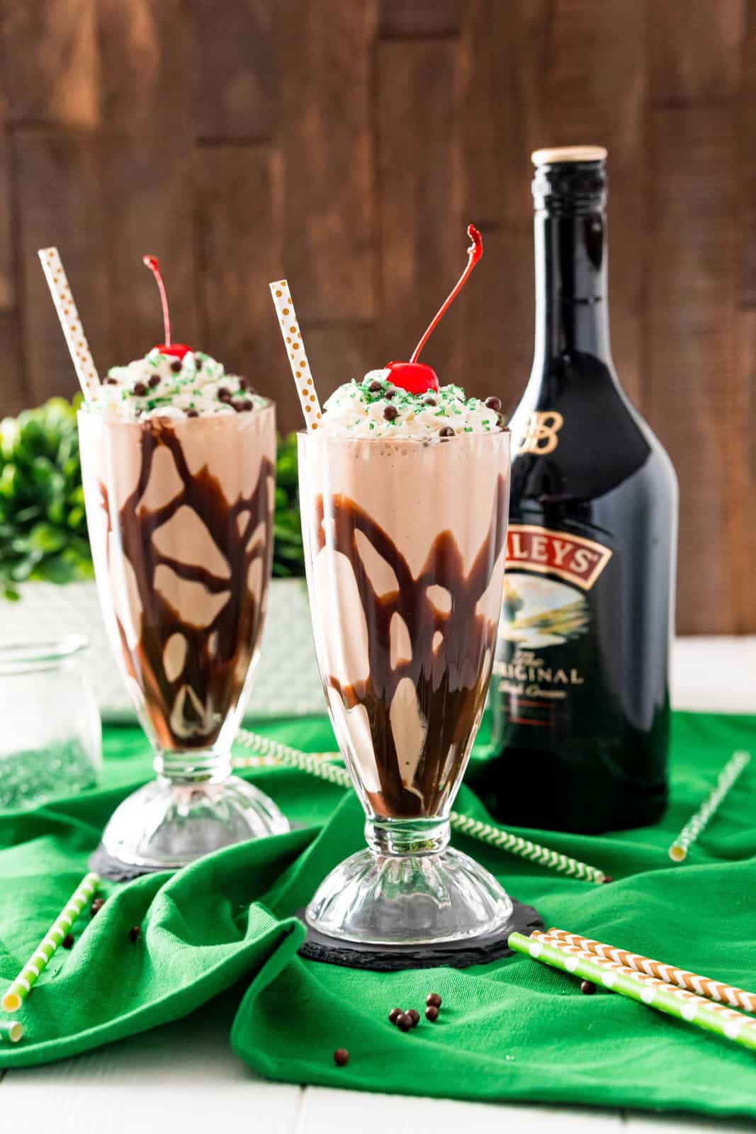 Two glasses of Chocolate Milkshake with Baileys bottle in background