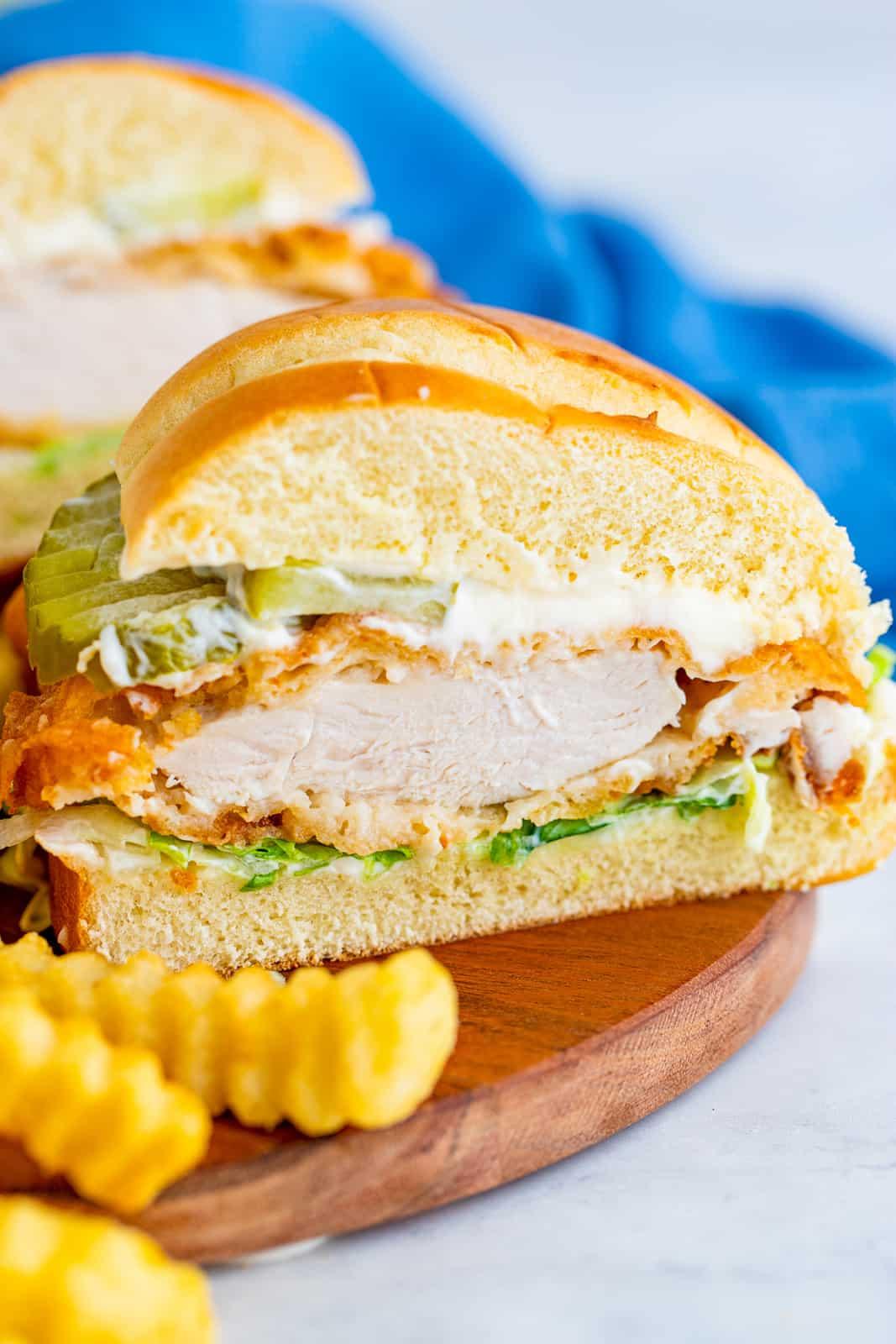 Close up of Chicken Sandwich cut in half on wooden board
