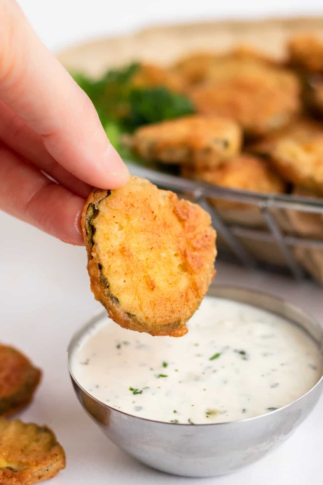 Hand dipping one pickle into ranch dressing