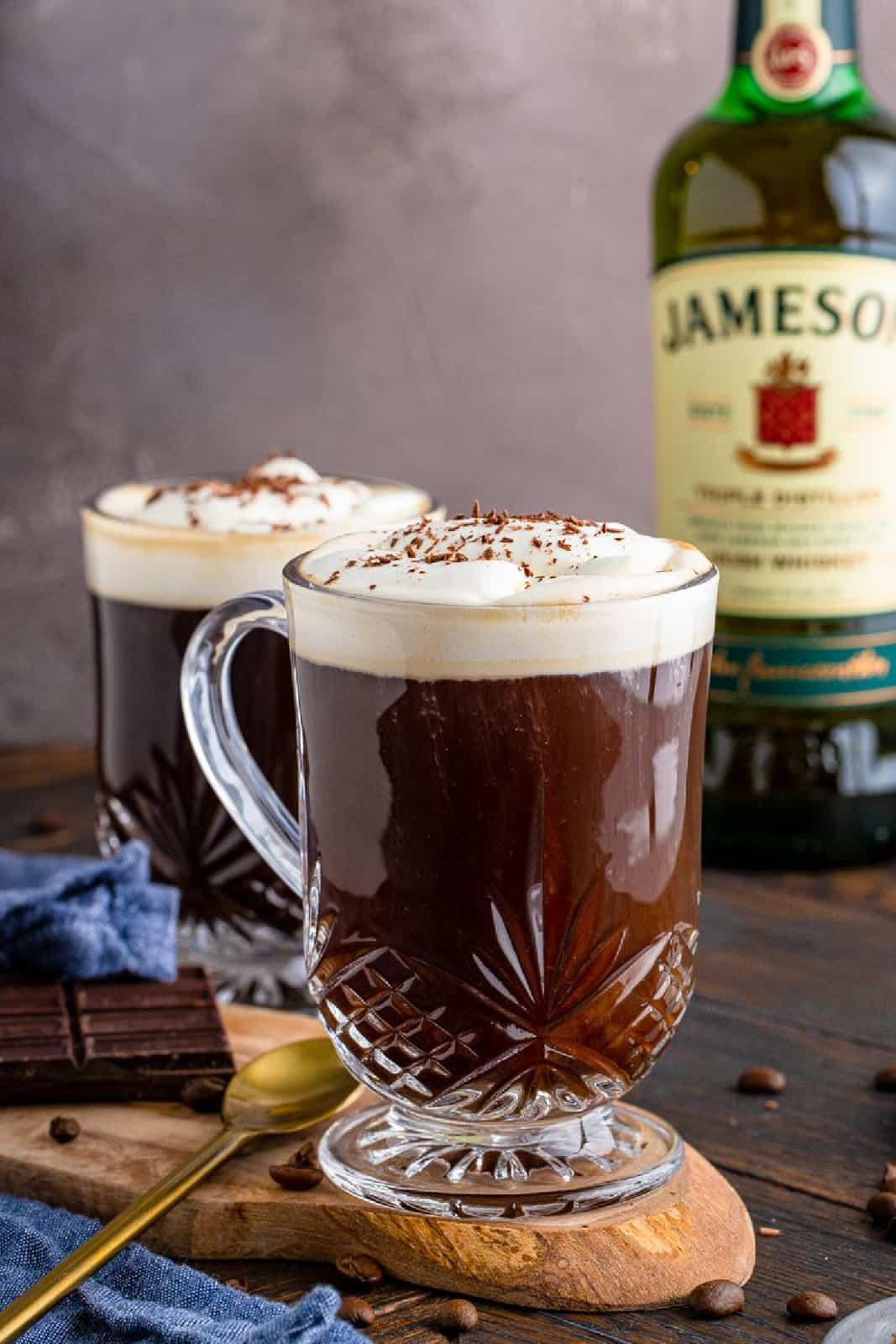 Two mugs of Irish Coffee with whiskey bottle in background