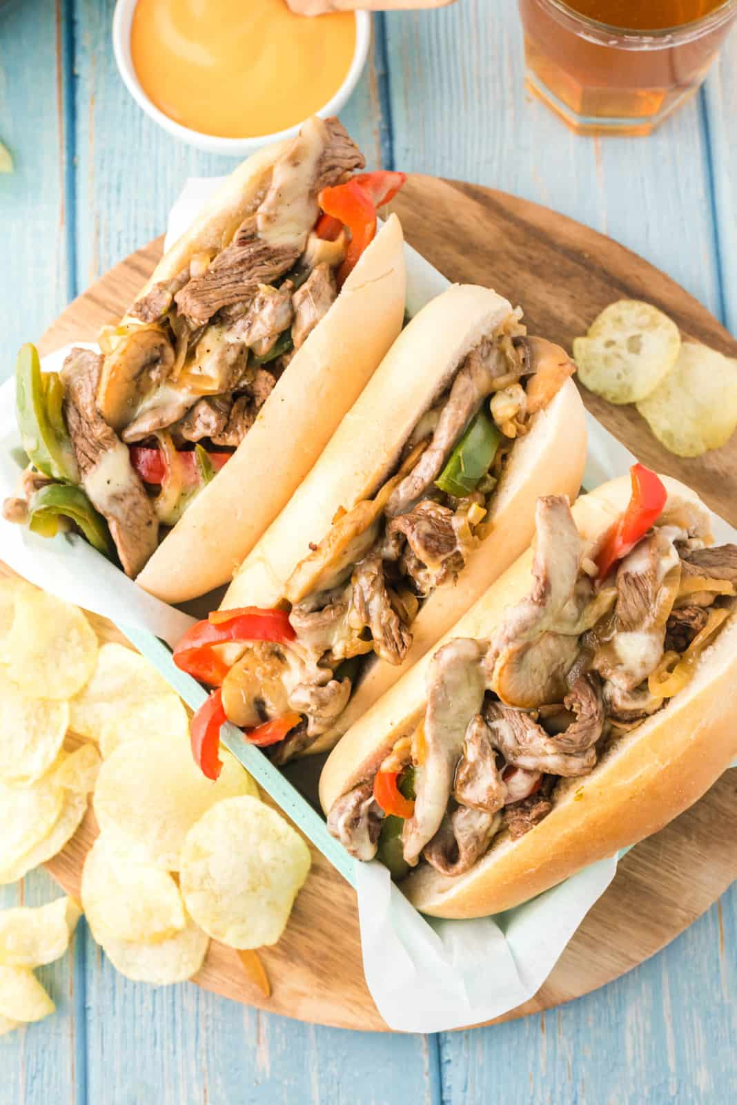 Overhead of three Philly Cheesesteaks lined up on tray