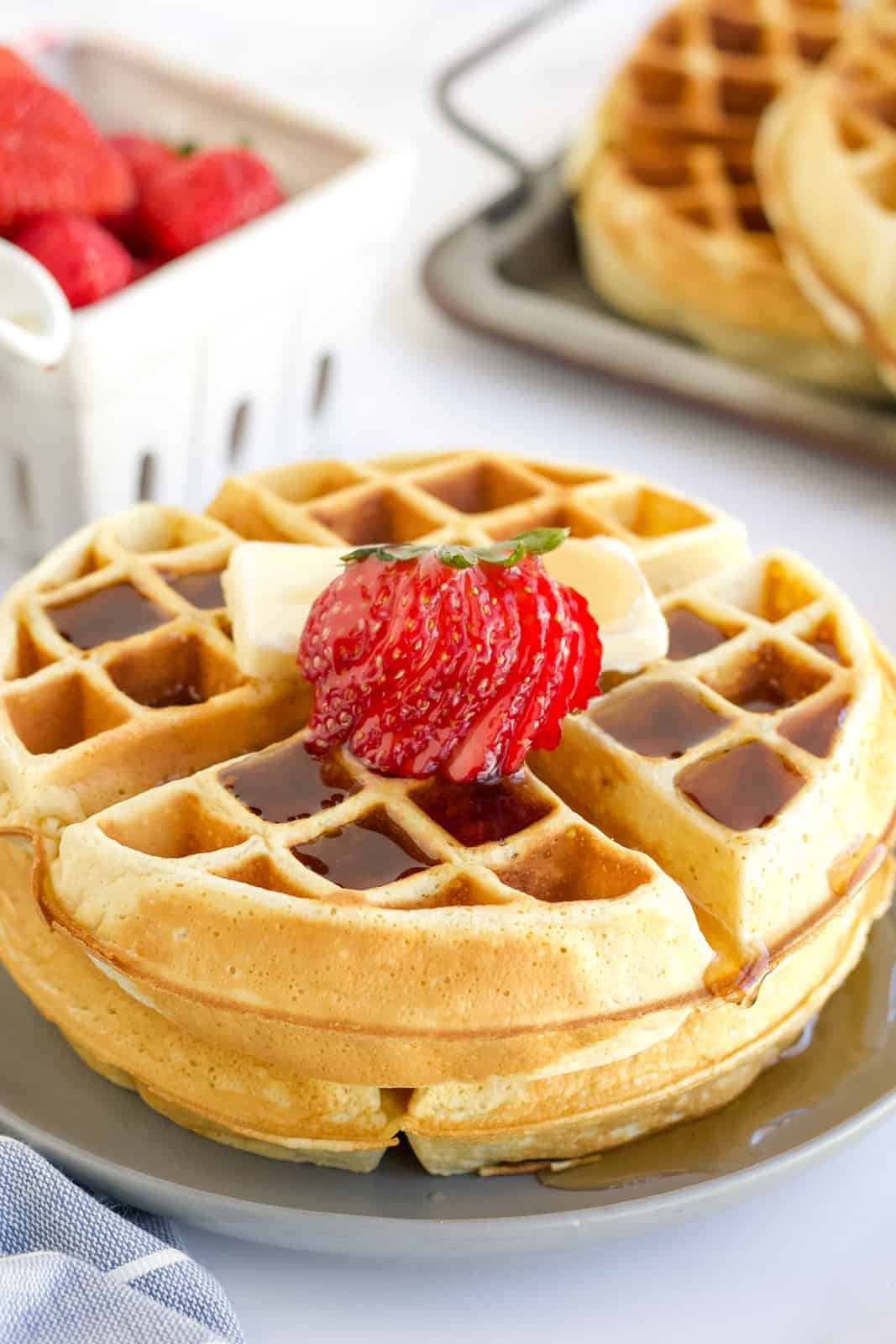 Two stacked Belgian Waffle Recipe with syrup, butter and strawberries