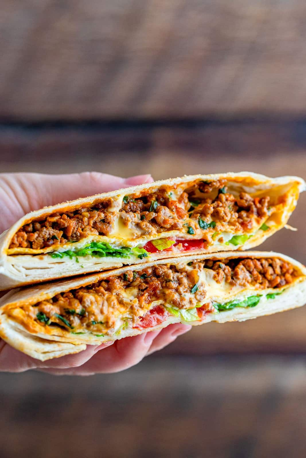 Hand holding up one cut Copycat Crunchwrap