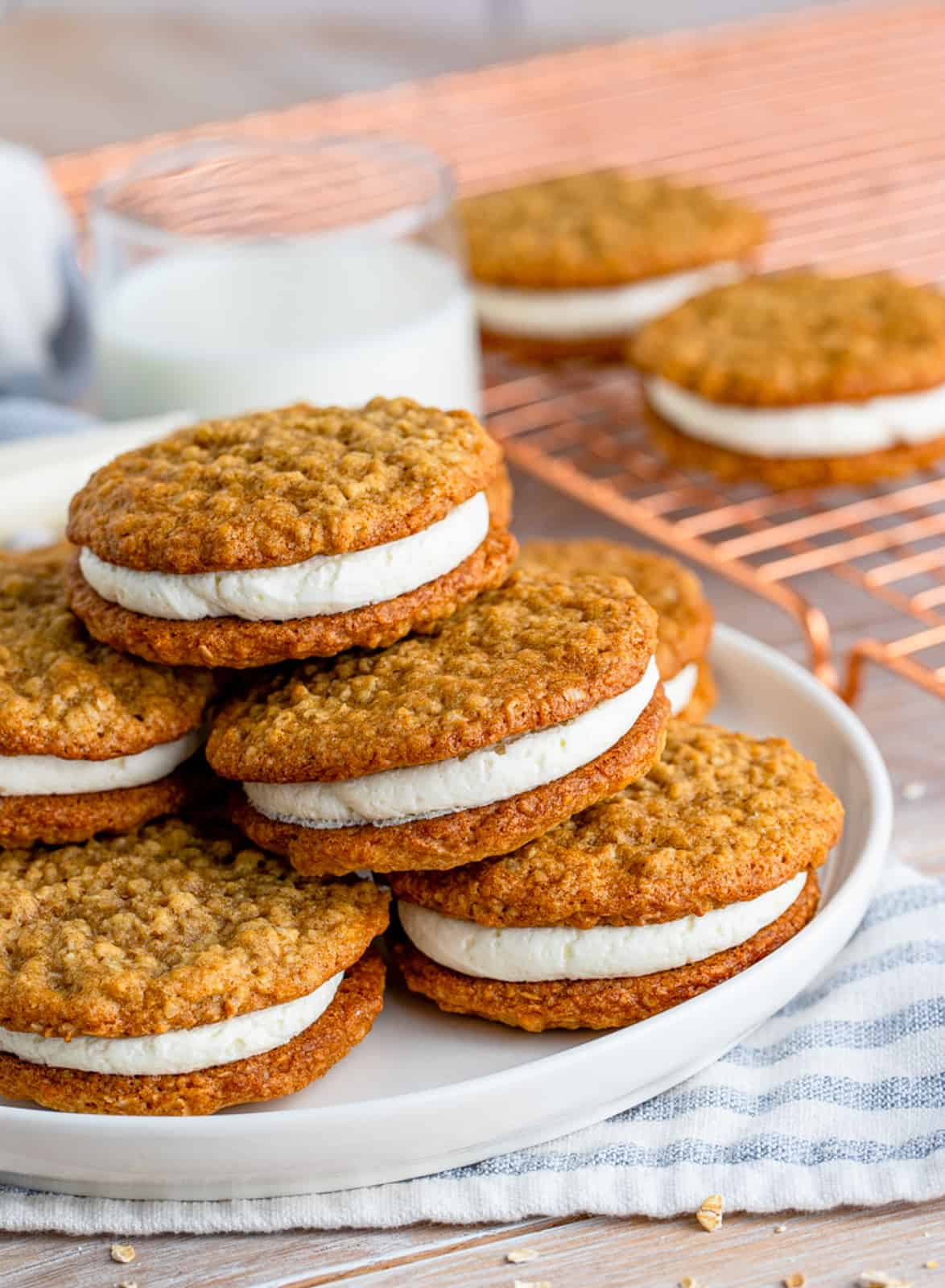 Oatmeal Cream Pies stacked on plate with milk in background