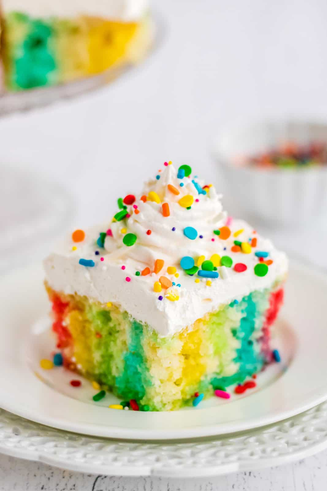 Slice of Jello Poke Cake on white plate topped with sprinkles