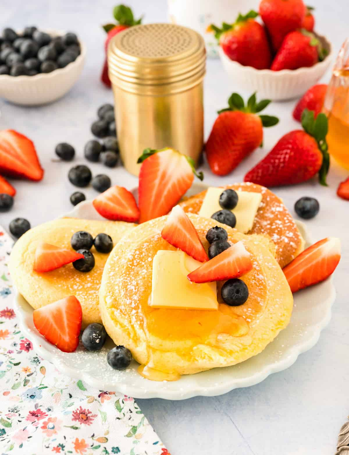 Soufflé Pancakes layered on plate with fruit and syrup
