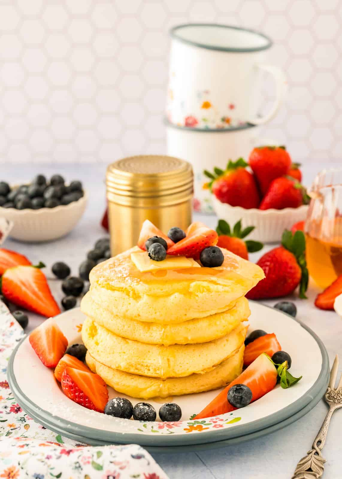 Stacked Soufflé Pancakes on plate with syrup and fruit