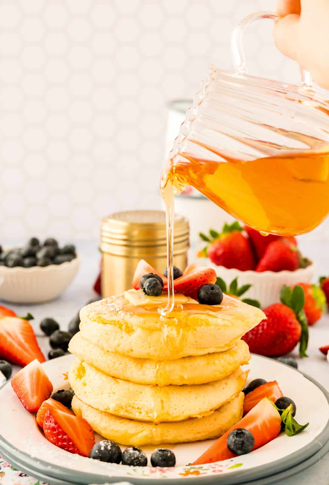 Stacked Pancakes on plate with syrup being poured over top