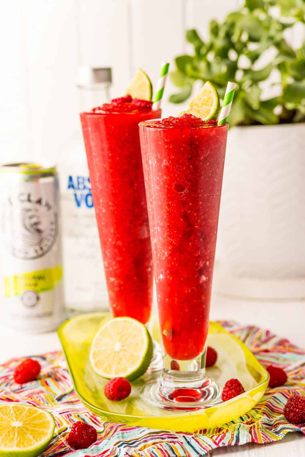 Two White Claw Slushies on platter with limes and raspberries