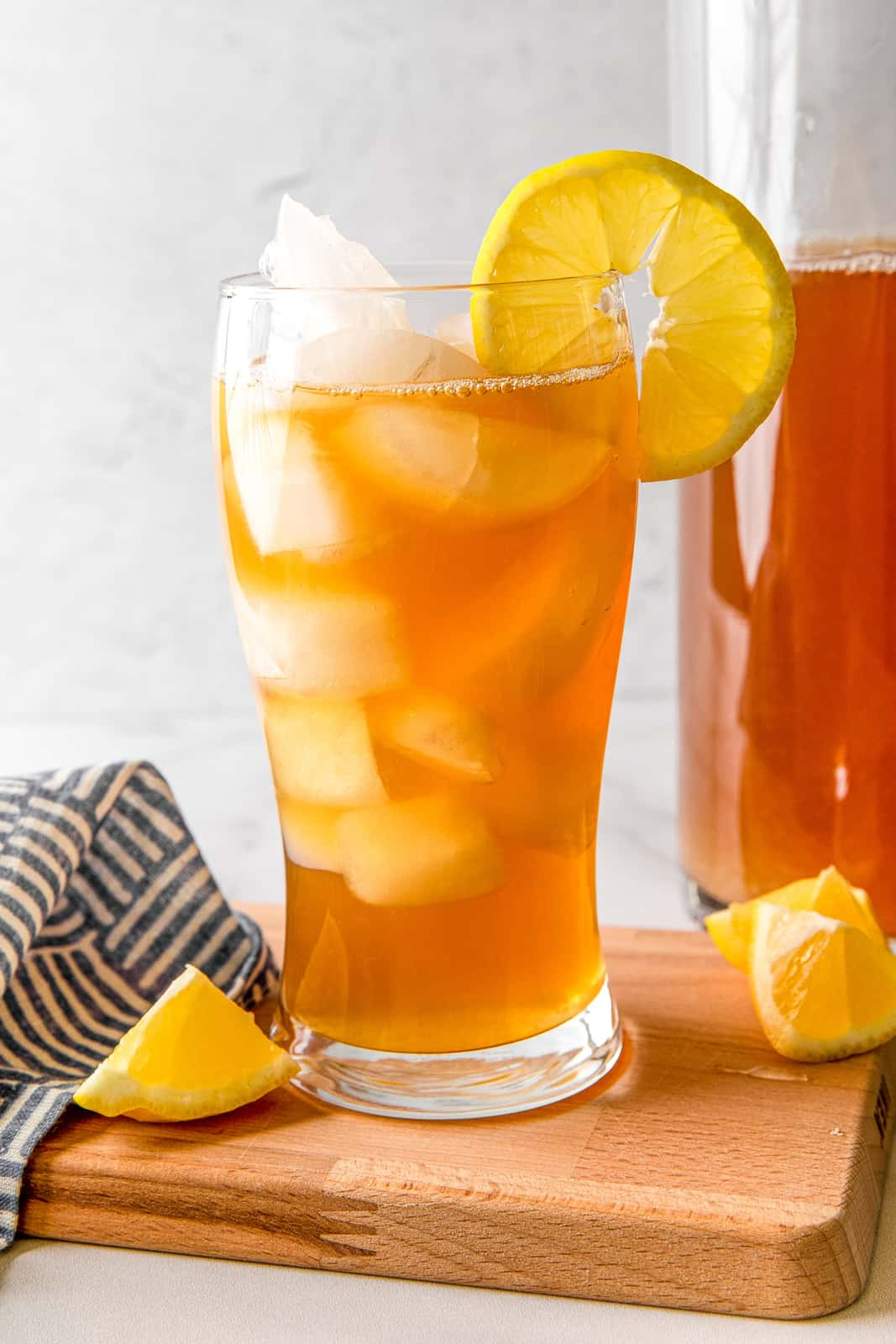 Close up of one Arnold Palmer Drink with lemon and pitcher in background