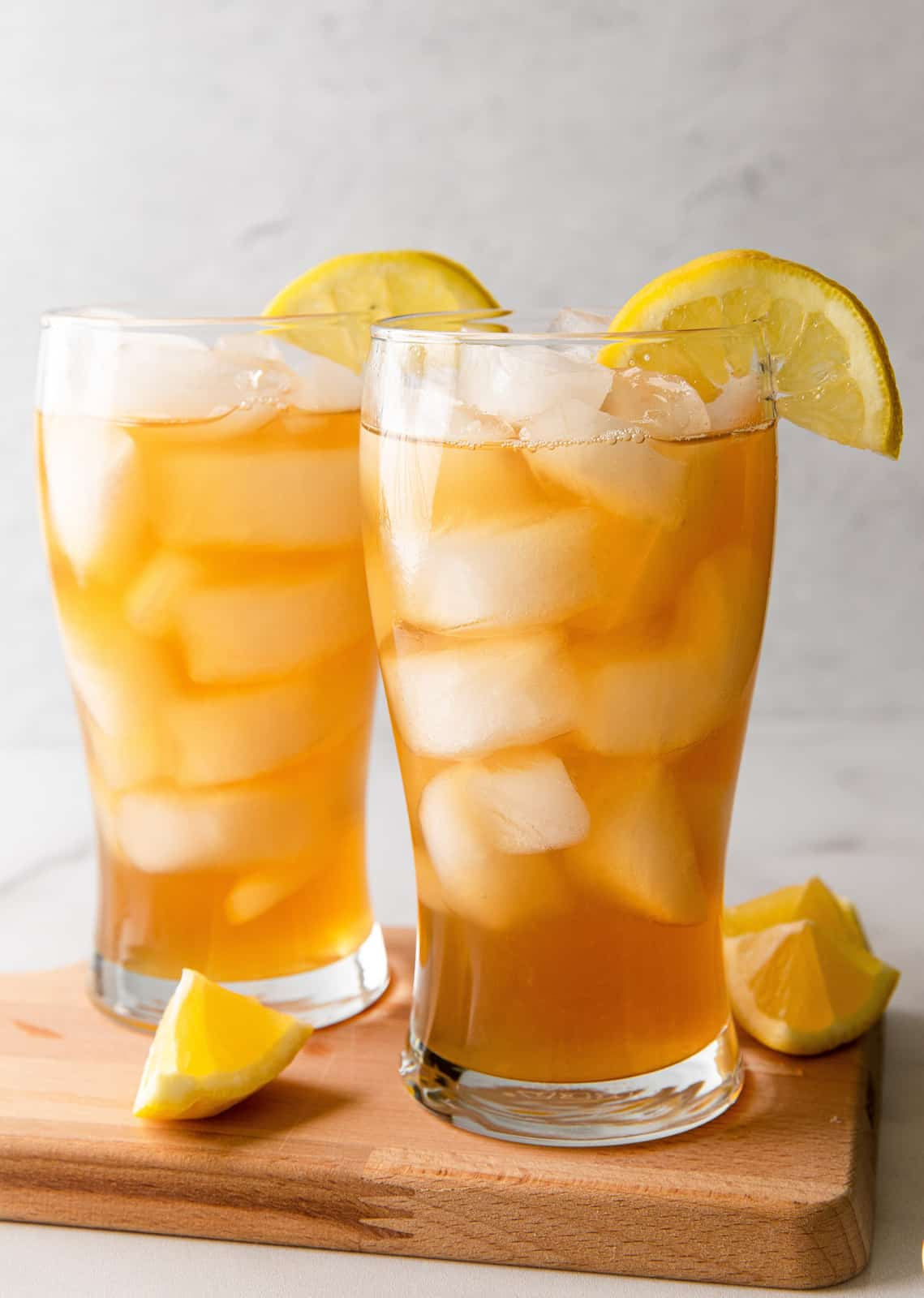 Two Arnold palmers with lemons on wooden board
