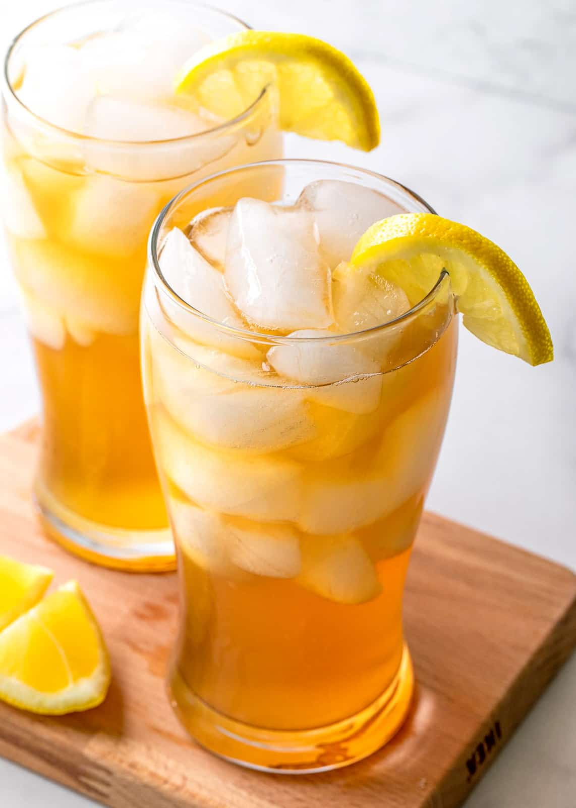 Slightly overhead photos of two Arnold Palmer Drinks with lemons and ice on wooden board