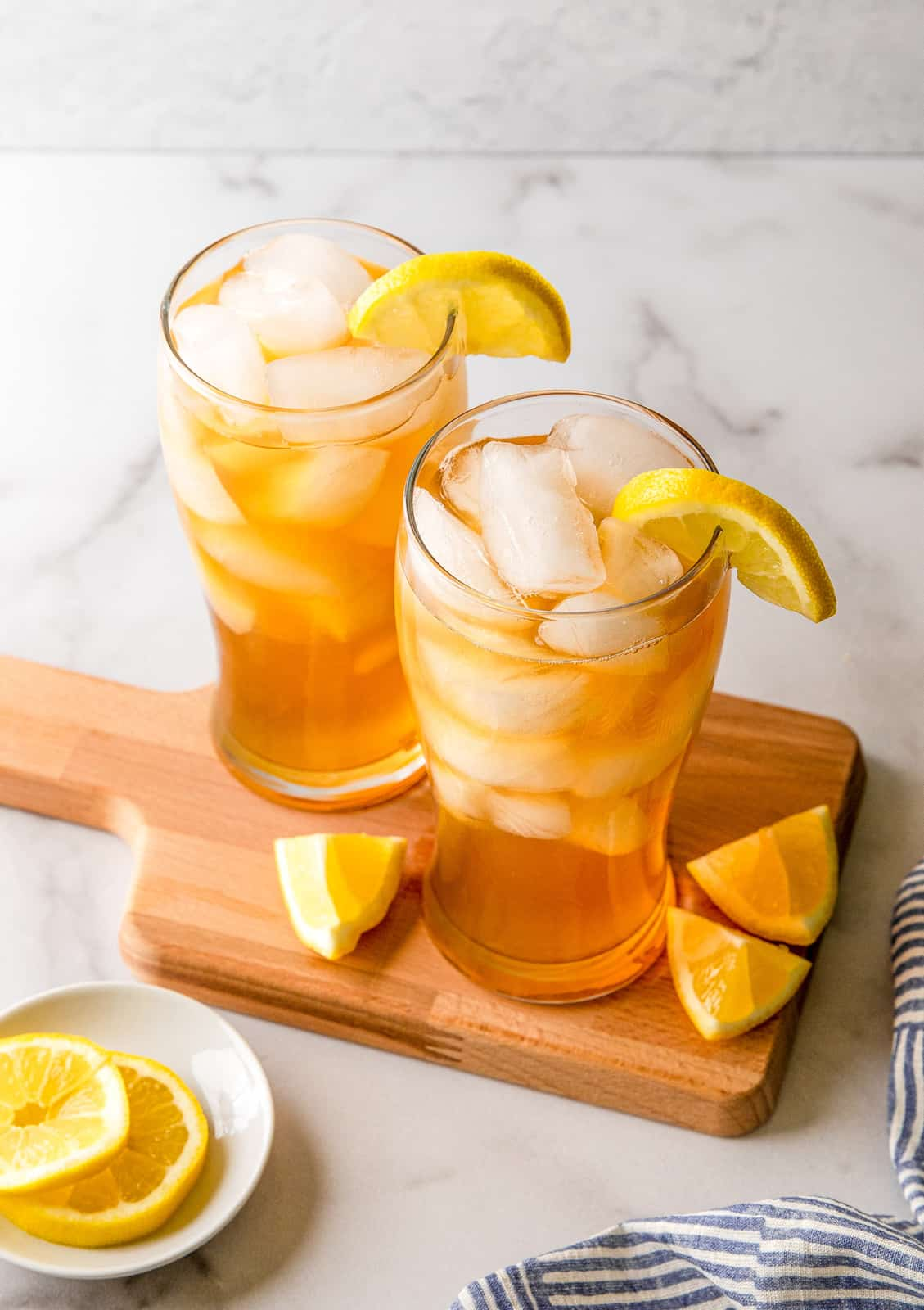 Two Arnold Palmers on wooden board surrounded by lemons