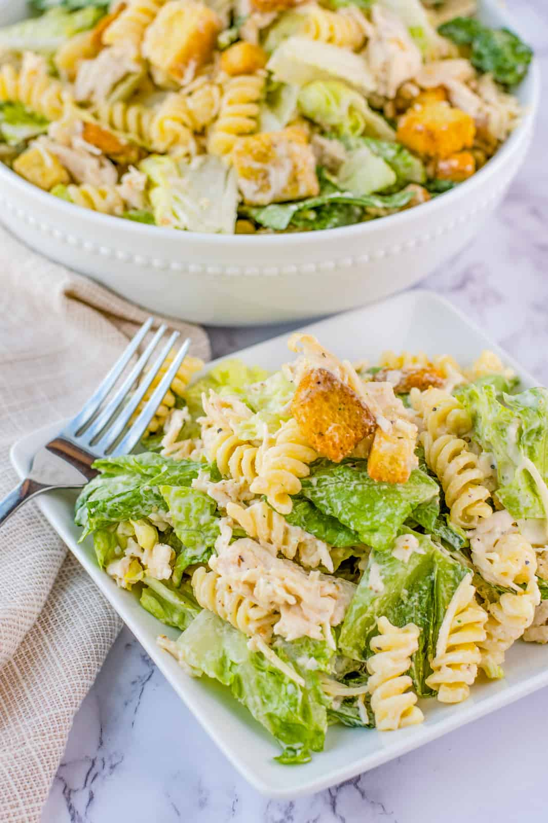 Square plate with Caesar Pasta salad with bowl of salad behind it