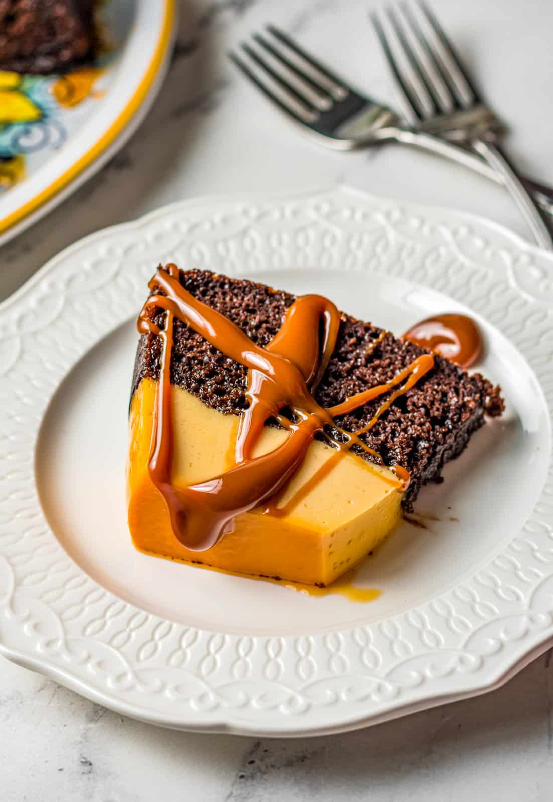 Chocoflan slice on white plate drizzled with dulce de leech