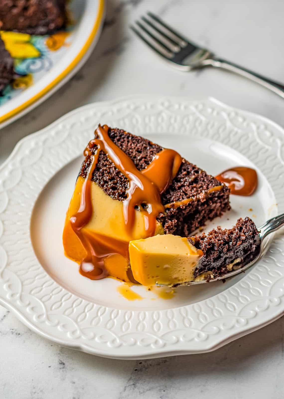 Slice of Chocoflan on white plate with dulce de leech with fork holding a bite