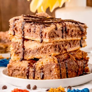 Side view of three Cheesecake Bars drizzled with chocolate syrup square image