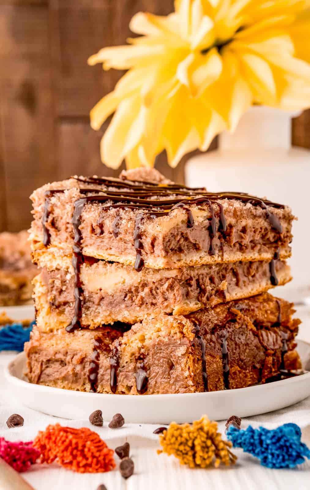 Chocolate Cheesecake Bars stacked three high and drizzled with chocolate syrup