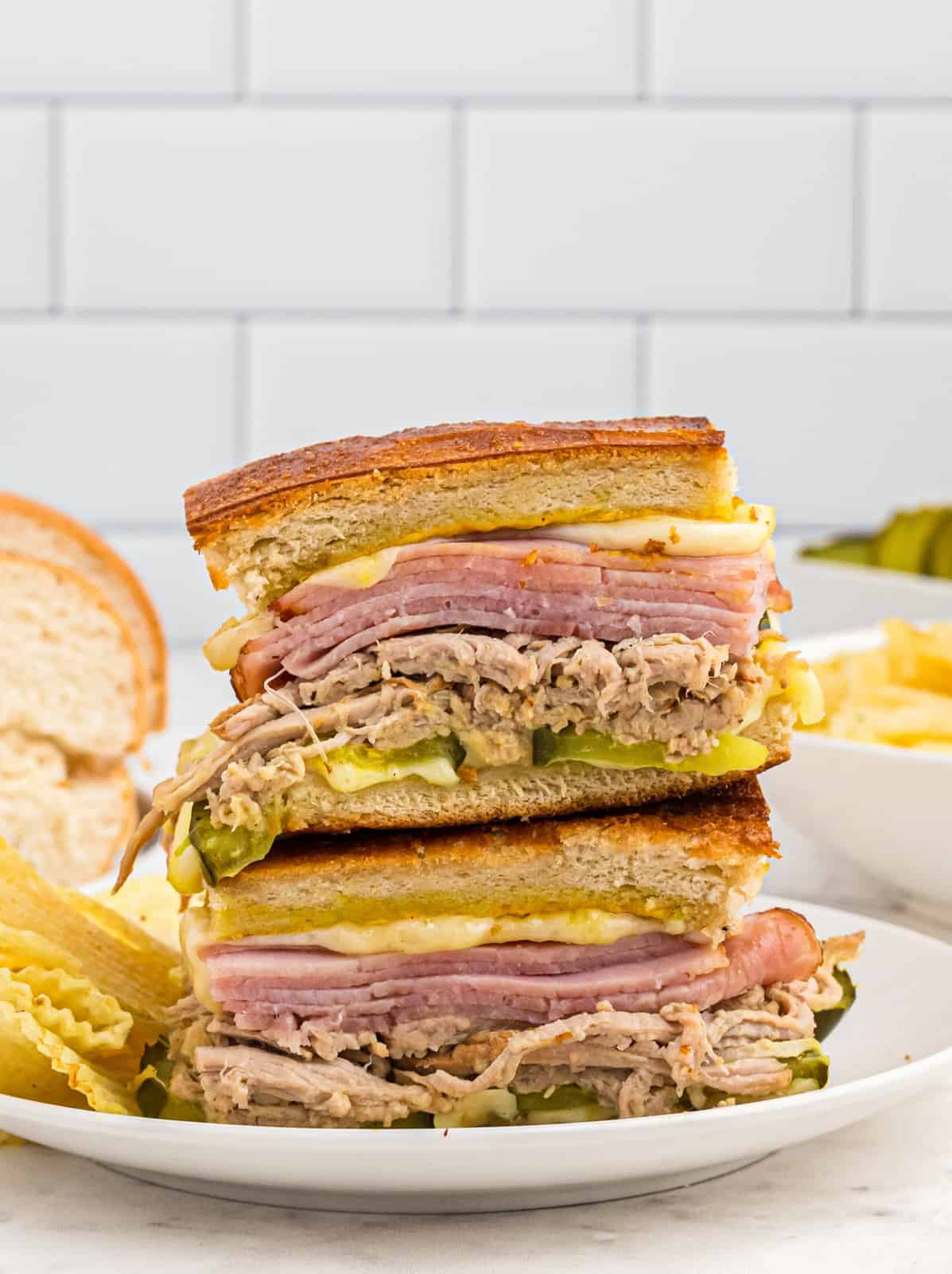 Two cut Cuban Sandwich Recipes stacked on plate
