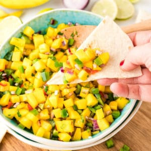 Hand scooping salsa out of dish with chip square image