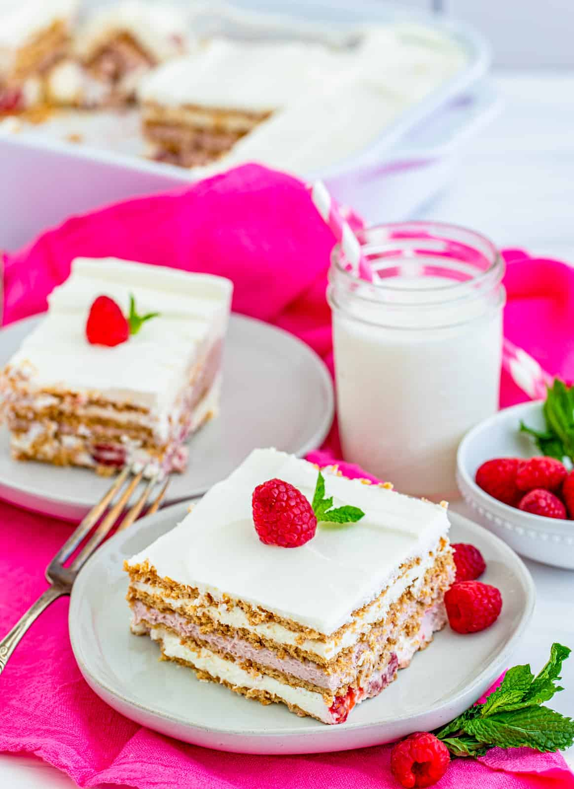 Two slices of cake on white plates topped with raspberries