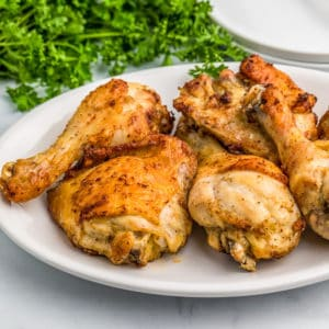 Close up photo of Air Fryer Chicken on white plate with parsley in background