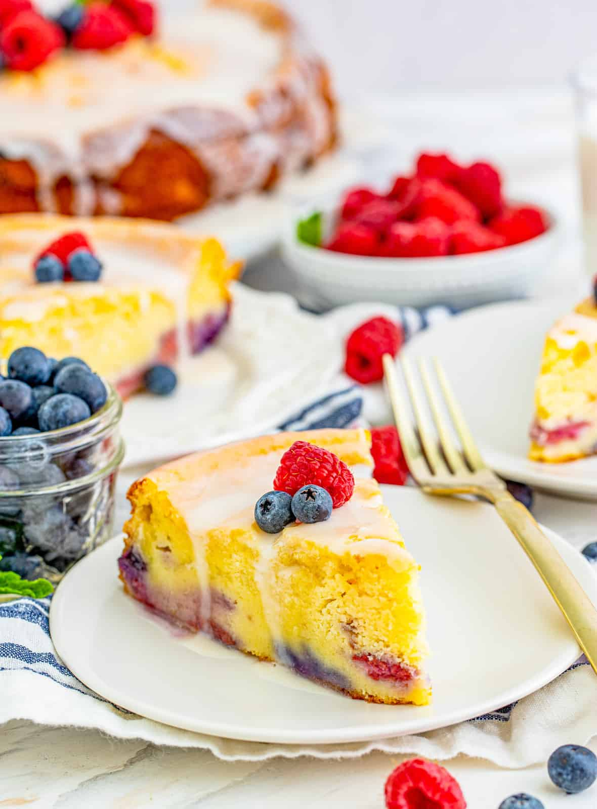Slices of Berry Ricotta Cake Ono plates topped with glaze and fruit