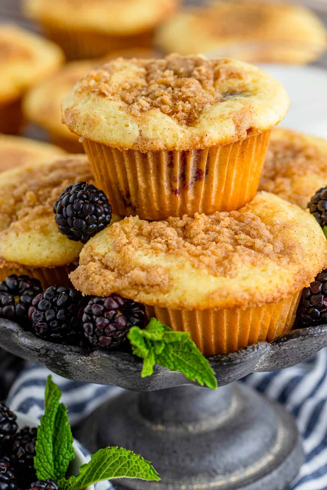 Stacked Blackberry Muffins on platter with fresh blackberries and mint