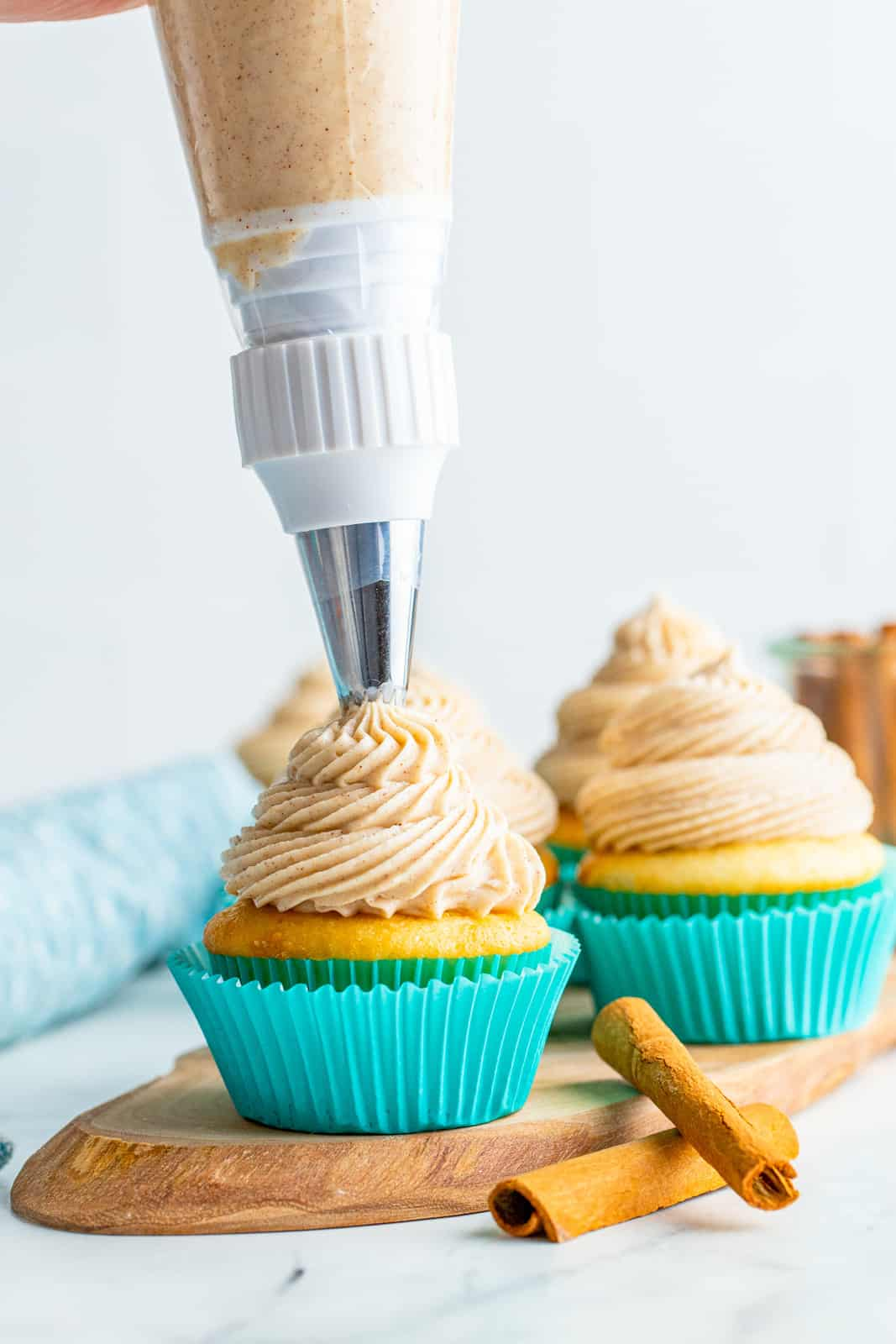 Pag piping Cinnamon Cream Cheese Frosting onto cupcake