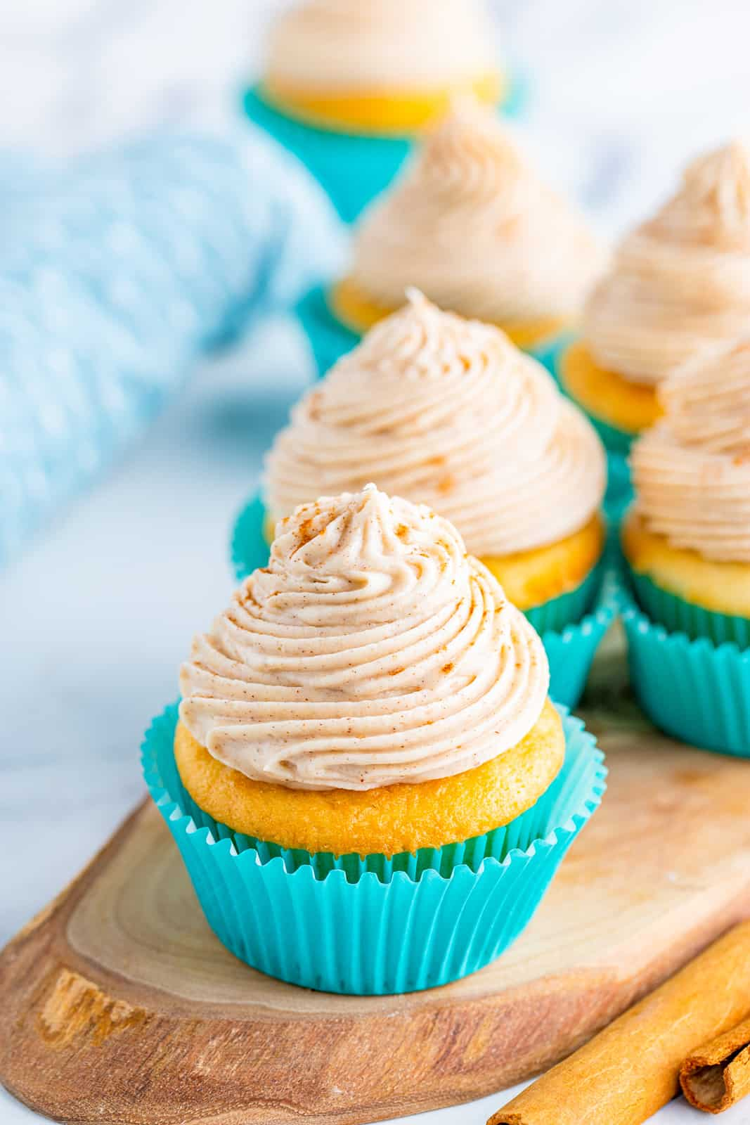 Cupcakes on wooden board topped with Cinnamon Cream Cheese Frosting