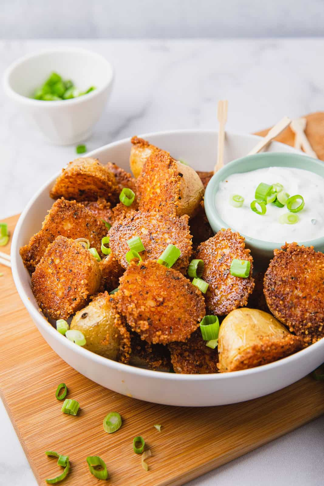 White bowl with Crispy Parmesan Potatoes with dipping sauce and green onions