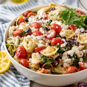 Square photo of finished pasta salad in white serving dish