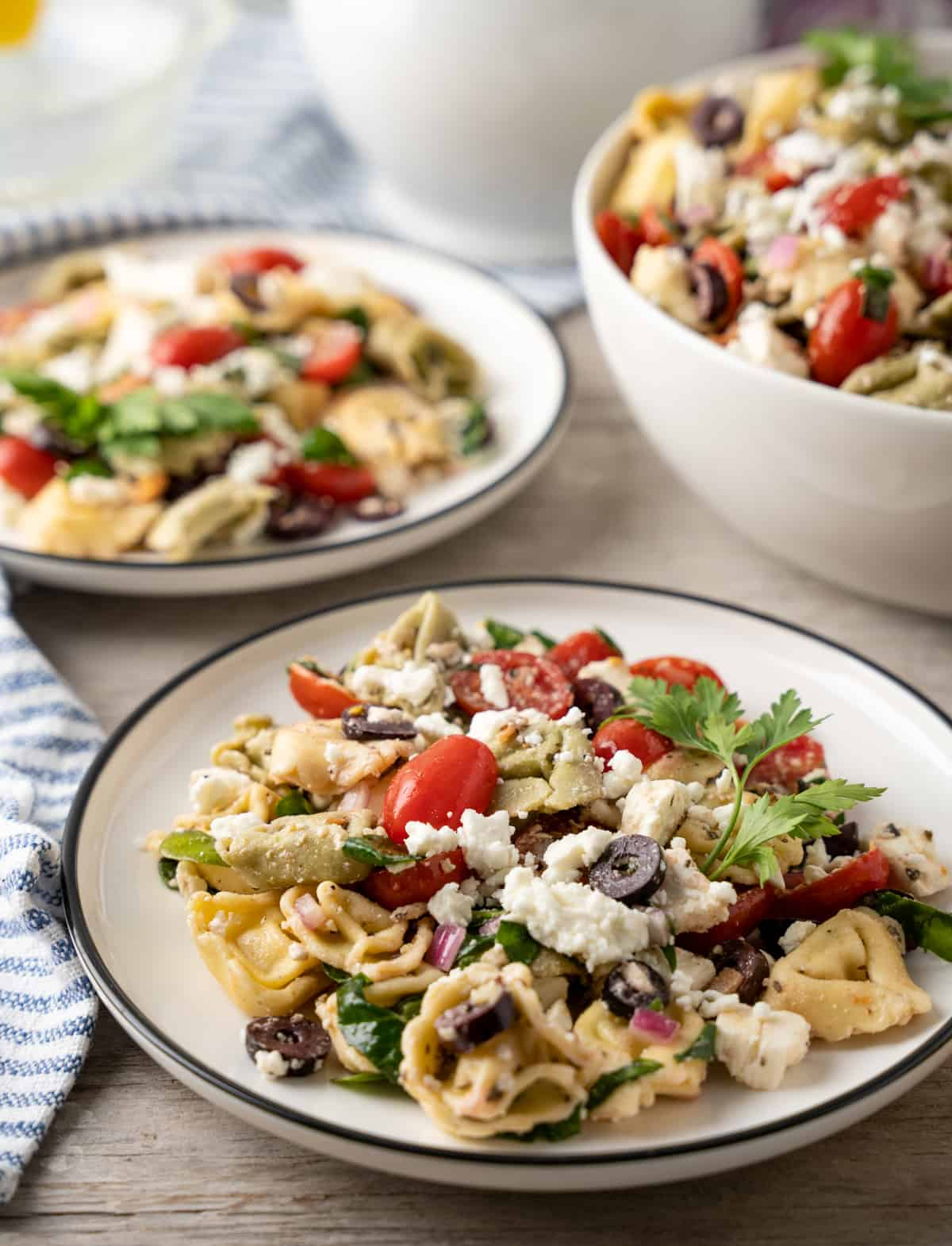 Two white plates with pasta salad on them with striped linen