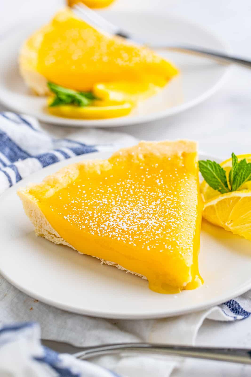 Slice of Lemon Tart on white plate with lemons and mint