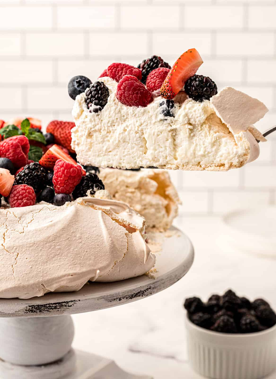 Pie server holding a slice out of the Pavlova recipe on cake stand