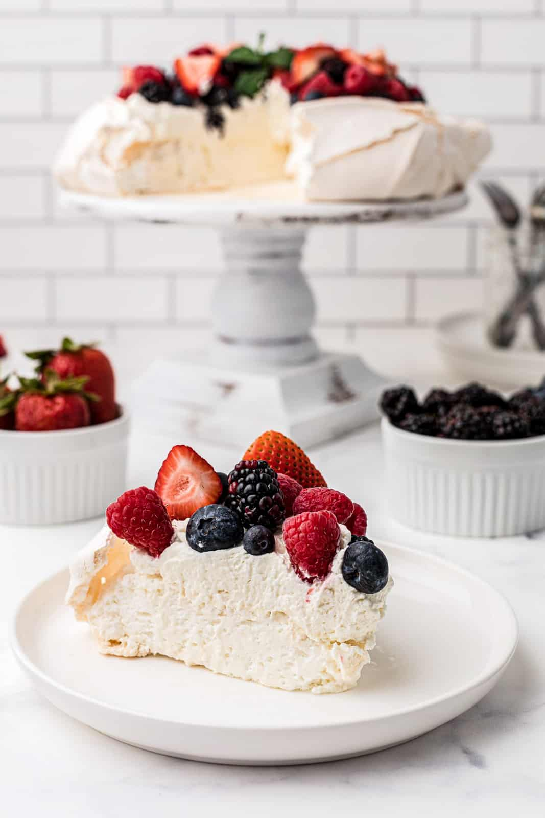 Slice of Pavlova on white plate with full Pavlova Recipe in background